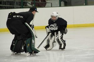 A young goalie and coach practicing