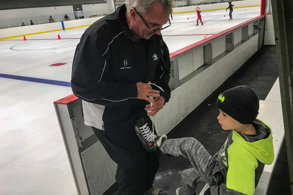 Adult helping child lace up ice skates